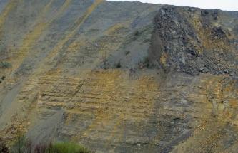 Ausschnitt aus einer Abbauwand in einem Steinbruch. Das anstehende Gestein ist in der oberen Hälfte dunkelgrau und in der unteren Hälfte schmutzig gelb. Vor allem im unteren Bereich ist eine horizontale Schichtung zu erkennen.