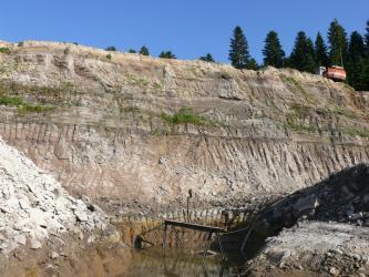 Blick auf die Abbauwand einer Sandgrube mit senkrechten Einkerbungen unten sowie in der Mitte der Wand. Links und rechts erheben sich Schutthügel. Am Fuß der Wand steht Wasser.