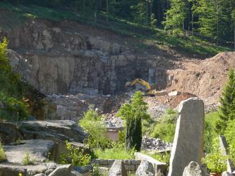 Blick in einen teilweise mit Büschen bewachsenen Steinbruch. Das anstehende Gestein wird auf mehreren Stufen abgebaut und hat eine rötlich graue Färbung.
