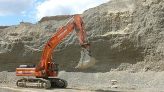 Das Bild zeigt eine hellgraue bis bräunlich graue, nach rechts ansteigende, sehr feinkörnige Steinbruchwand. Links vor der Wand steht ein orangeroter Bagger.