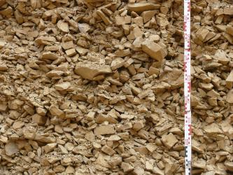 Nahaufnahme von kleinen bis größeren, rötlich braunen Steinen. Die Steine sind über mehrere Zentimeter aufgetürmt und bilden so eine Wand.