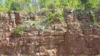 Blick auf rötlich graue Gesteinswände, links etwas hervorstehend und im oberen Teil bewachsen.