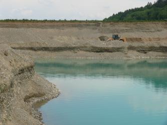 Blick auf die waagrecht verlaufende Wand einer Kiesgrube mit Schaufellader und vorne anstehendem See. Links schiebt sich eine weitere Abbauwand ins Bild.