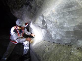 Ein Bergbauarbeiter links im Bild beschäftigt sich mit einer Wand aus großen, weißlichen Kristallen, die auf grünlichem Gestein aufliegt.