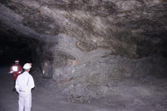 Gezeigt wird eine große, grau und schwarz marmorierte Steinsalzwand unter Tage.