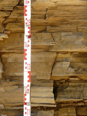 Nahaufnahme von rötlich braunem Gestein, das in dünnen Lagen gleichmäßig aufeinandergeschichtet ist.