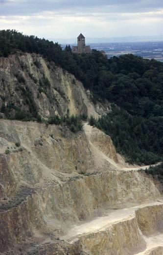 Blick von seitlich oben auf einen Steinbruch mit mehreren Abbausohlen. Das Gestein ist hellgrau und leicht gelblich. Von oben und rechts ist der Steinbruch von dunklem Wald begrenzt. Über dem Steinbruch steht eine kleine Burg.