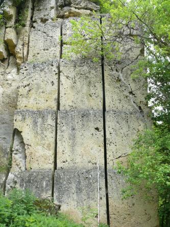 Blick auf eine steil aufragende, hellgraue Gesteinswand. Horizontale, durchgehende Schnitte im Gestein deuten auf Sägearbeiten hin. Die Frontseiten des Gesteins sind ebenfalls bearbeitet.