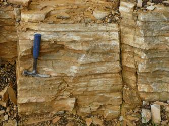 Nahaufnahme von rötlich braunen, plattigen Gesteinsblöcken. Die Blöcke weisen oben und unten Abbruchstellen auf. Ein links aufgestellter Hammer dient als Größenvergleich.