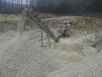 In der Bildmitte ist der maschinelle Abbau von Kiesen und Sanden durch einen Bagger zu sehen. Das Material wird auf ein Förderband gebracht und im Vordergrund des Bildes zu einem Hügel aufgeschüttet.