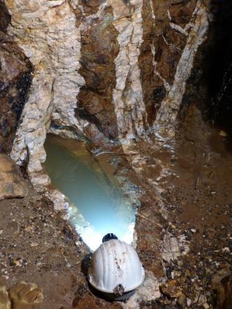 Blick auf einen dunkelbraunen Grubengang in einem Bergwerk. Von einem Helm ausgehend, der unten abgelegt wurde, und einer angrenzenden ovalen Wasserfläche, breiten sich wie Federn weißliche und braune Adern nach oben aus.