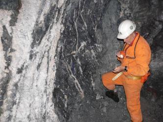 Blick auf einen Schwerspatgang in der Grube Clara. Rechts ein Bergbaumitarbeiter in oranger Schutzkleidung.