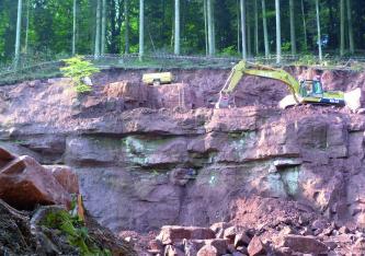 Blick auf eine Abbauwand in einem Steinbruch im Wald. Das anstehende Gestein ist dunkelrot und an manchen Stellen grünlich verfärbt. Vor der Wand auf dem Boden liegen einige kleinere Blöcke. Oben rechts steht ein Bagger.