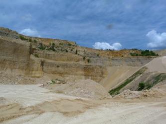 Der Betrachter befindet sich in einem Steinbruch aus hellbeigem Gestein, welches auf mehreren Sohlen abgebaut wird. Die obere Bildhälfte wird von intensiv blauem Himmel eingenommen.