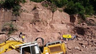 Blick in einen Steinbruch. Im Vordergrund links ist ein gelber Bagger zu sehen, etwas weiter hinten befindet sich ein weiteres Baustellenfahrzeug und ein Mensch. Die Abbauwand ist gestuft, das Gestein hellrot und geklüftet. Über der Wand wachsen Büsche.