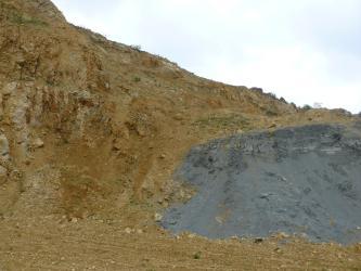 Blick auf eine Gesteinswand, deren Oberkante von links oben bis rechts mittig durch das Bild verläuft. Das anstehende Gestein ist in den linken zwei Dritteln dunkelgelb bis braun, rechts dagegen mittelgrau.