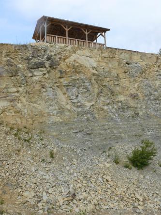 Blick von seitlich unten auf eine Gesteinswand, welche den Übergang zwischen bankigem, hellbeigem Gestein (oben) und massigem, grauem Gestein (unten) zeigt. Über der Wand steht eine offene Hütte aus Holz.