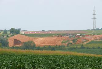 Inmitten einer grünen Nutzlandschaft befindet sich in der Bildmitte eine Lehm- und Tongrube. Das anstehende Gestein ist rötlich-braun.