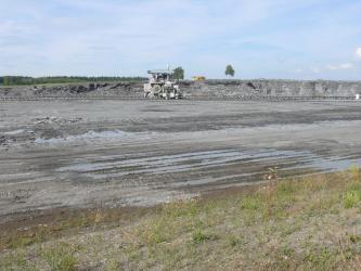 Blick auf eine flache, von Wasser durchzogene graue Bodenfläche. Im Hintergrund erhebt sich eine niedrige Steinbruchwand. Davor ist eine auf Transportschienen laufende Maschine zu sehen. Im Vordergrund folgt von Gras durchsetzter Boden.