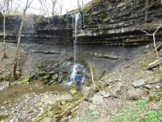 Über dunkle, waagrecht gebankte Gesteinsschichten rinnt ein dünner Wasserfall. Unterhalb der Deckschichten ist ein nach innen geneigter Hang zu sehen. An dessen Fuß sammelt sich das Wasser, begleitet von angehäuften Gesteinsbrocken.