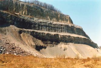 Blick von der Seite auf eine alte, schön gestufte Abbauwand eines Steinbruchs. Das anstehende Gestein zeigt eine deutliche Schichtung. Unter den drei Stufen befindet sich eine Schräge aus Geröll.