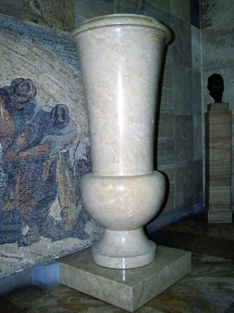Das Bild zeigt eine sehr große, beigefarbene Vase. Die aus drei unterschiedlichen Teilen (Fuß, rundes Mittelstück und trichterförmige Öffnung) bestehende, marmorierte Vase steht auf einem niedrigen Podest.
