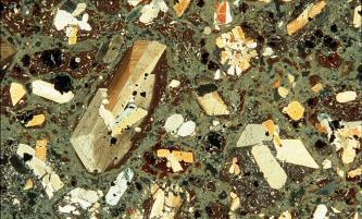 Das Dünnschliffbild zeigt gelblich-weiße bis braune längliche Kristalle, die sich in einer teils rostbraunen, teils graugrüner Grundmasse befinden.