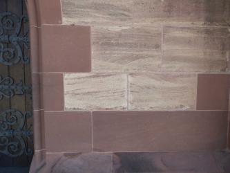 Mauer aus dunkelroten, homogenen Sandsteinblöcken und helleren, gebänderten Sandsteinblöcken. Am linken Bildrand ist ein Teil eines Eisentors zu sehen.