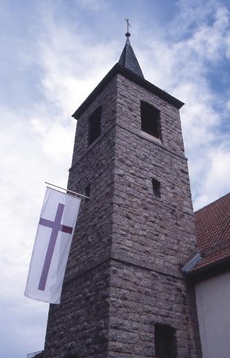 Blick von unten auf einen viereckigen Kirchturm mit spitzem Dach. Der Turm ist aus rötlichem Gestein gebaut. Auf der linken Seite des Turms ist eine weiße Fahne mit rotem Kreuz angebracht.