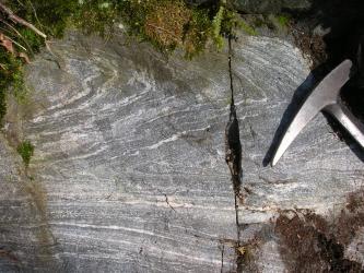 Nahaufnahme von grauem Gestein mit weißen, teils horizontal, teils wellenartig verlaufenden Streifen. Rechts, neben einem Hammer, verläuft ein vertikaler Riss durch das Gestein. Oben ist Moos erkennbar.