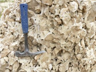 Großaufnahme von unregelmäßig geformtem, hellbraunem Gesteinsschutt. Ein Hammer links dient als Größenvergleich.