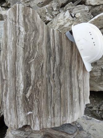 Das Foto zeigt einen hellgrau und dunkelgrau gestreiften Gesteinsblock. Die äußeren Kanten sind unregelmäßig gebrochen. Ein weißer Schutzhelm dient als Größenvergleich.