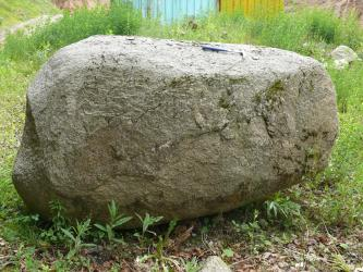 Rundlicher, leicht länglicher Findling aus grauem Gestein auf einer Wiese.
