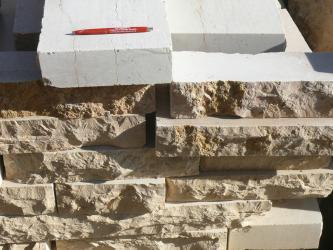 Das Foto zeigt mehrere übereinander gestapelte Platten aus gelblich-beigem Gestein. Darüber liegt eine schräggestellte, weiße Platte mit einem roten Kuli darauf.