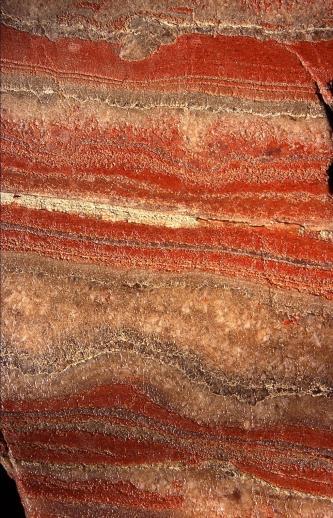 Nahaufnahme von Kalisalz mit waagrechten Streifen in rot, weiß und grau.