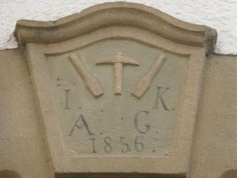 Kunstvoll gefertigtes Türschild mit Werkzeugen, Buchstaben und Jahreszahl darauf. Das Schild ist aus homogenem, beigem Kalkstein gefertigt.