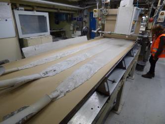Perspektivische Aufnahme einer Maschine mit Auflagefläche. Auf dieser Fläche liegt eine hellbraune, große Platte. Aus drei Schlauchöffnungen links fließt weißlicher, flacher Brei auf die Platte und verteilt sich dort gleichmäßig.