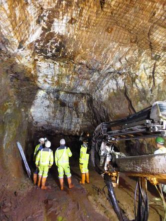 Blick in das Innere eines Bergwerks. Zu sehen ist ein breiter, gut ausgeleuchteter Stollen mit hoher Decke sowie ein ins Dunkel führender Schacht. Mehrere Personen in gelber Schutzkleidung stehen davor.