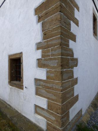 Das Foto zeigt die aus rötlich grauen Mauersteinen gefertigte Ecke eines Hauses. Die nach links und rechts abgehenden Wände des Gebäudes sind weiß.