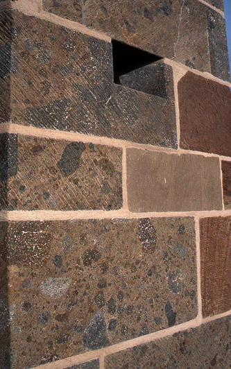Teilansicht eines rötlichen bis bläulich grauen Mauerwerks mit hellen Fugen und dunkleren Einschlüssen.