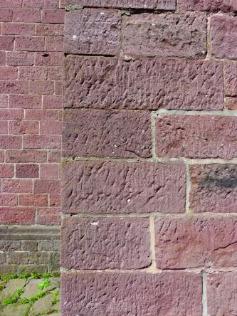 Das Bild zeigt Mauerwerk aus dunkelrotem, geröllführendem Sandstein mit hellen Fugen.