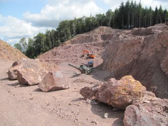 Blick über im Vordergrund verteilte große Steinblöcke auf eine nach links abfallende, rötlich graue Steinbruchwand mit mehreren Sohlen. Eine weitere Wand rechts liegt im Schatten. Im Mittelgrund ist ein Bagger sowie ein Förderband im Einsatz.