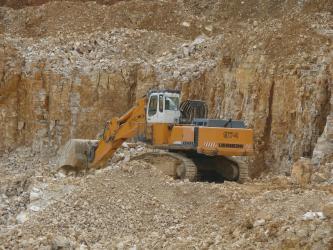 Das Bild zeigt einen gelben Bagger vor einer rötlich braunen Steinbruchwand. Im Vordergrund befindet sich eine Abraumhalde.