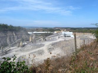 Blick über einen Drahtzaun auf ein ausgedehntes Steinbruchgelände. Auf einem Plateau, zwischen Fahrwegen und Abraumhalden, stehen Förderbänder. Links ragt eine Bruchwand auf, rechts geht es tiefer hinab. Im Hintergrund liegen bewaldete Hügel.