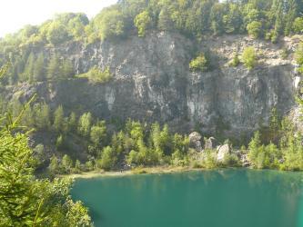 Blick auf eine im Gegenlicht fotografierte, graue Steinbruchwand. Das Gestein ist am Fuß, an der Kuppe und auch in der Wand von Bäumen und Sträuchern bewachsen. Am Fuß der hohen Wand liegt zudem ein grüner See.
