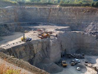 Blick von oben in einen abgestuften Steinbruch. Rechts unten ist der Boden sichtbar, mit Lastwagen und Radlader. Nach links hin steigt eine höhere Sohle auf, ebenfalls mit Fördergeräten, zum Hintergrund eine noch höhere Bruchwand.