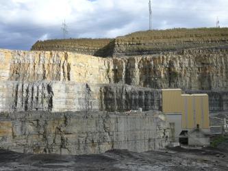 Blick auf mehrere, wie Kulissen hintereinander aufgereihte Abbauwände in einem Steinbruch. An die vorderste, niedrigste Wand ist rechts eine Förderanlage angebaut. Die Farben der Bruchwände wechseln von dunkelgrau bis rötlich braun.