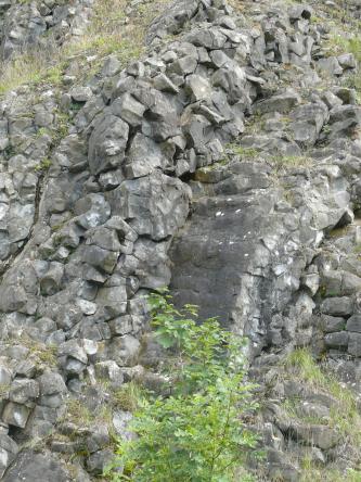 Auf diesem Bild liegen an einem Hang abwärts graue bis dunkelgraue Steinbrocken bogenförmig aufeinander und bilden dabei fast eine Art Rutschbahn.