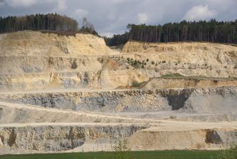Schöner Blick auf mehrere Sohlen eines Steinbruches, mit einer Auffahrtrampe links unten. Die Farbe des Gesteins ist vorherrschend gelblich braun mit grauen Stellen. Die Kuppe oben ist bewaldet.