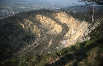 Seitlicher Blick über die Abbruchkante eines alten Steinbruches. Drei nach links unten führende, jeweils niedrigere Sohlen sowie Schutthaufen und schmale Wege sind noch zu erkennen. Unten und an den Rändern im Hintergrund stehen Bäume.